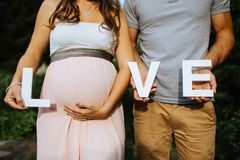 pregnant woman and her husband holding the letters for love in their hands with royalty free stock image