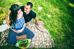 Pregnant women with her husband outdoor in the park with basket Stock Photos