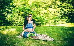 Pregnant women with her husband outdoor in the park with basket Royalty Free Stock Photography