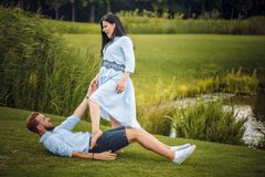 Pregnant woman and her husband in a park near the water hugging stock photography
