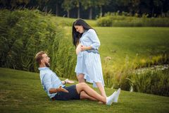 Pregnant woman and her husband in a park near the water hugging royalty free stock images