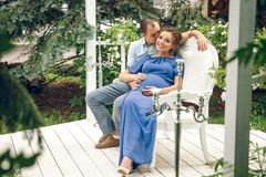 Pregnant woman and her husband sitting and hugging at cozy cafe terrace in the fall. stock photos