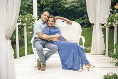 Pregnant woman and her husband sitting and hugging at cozy cafe terrace in the fall. royalty free stock image