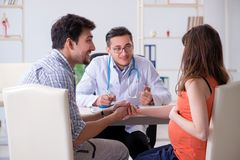 The pregnant woman with her husband visiting the doctor in clinic Royalty Free Stock Images