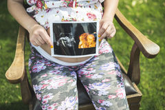 Pregnant women hold picture of womb Stock Photography