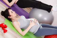 Pregnant women with large gymnastic balls. Two happy pregnant women,brunette and blonde,dressed in sportswear,execute a complex of exercises for pregnant women stock photography