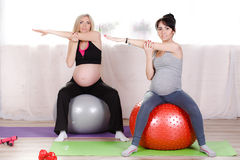 Pregnant women with large gymnastic balls. Two happy pregnant women,brunette and blonde,dressed in sportswear,execute a complex of exercises for pregnant women royalty free stock photo