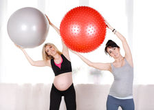 Pregnant women with large gymnastic balls. Two happy pregnant women,brunette and blonde,dressed in sportswear,execute a complex of exercises for pregnant women stock image