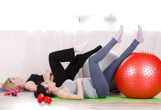 Pregnant women with large gymnastic balls. Two happy pregnant women,brunette and blonde,dressed in sportswear,execute a complex of exercises for pregnant women royalty free stock photos