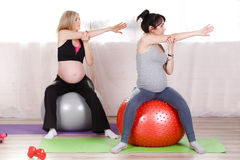 Pregnant women with large gymnastic balls. Two happy pregnant women,brunette and blonde,dressed in sportswear,execute a complex of exercises for pregnant women stock photo