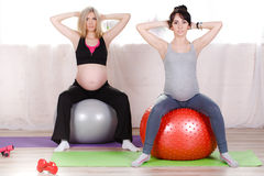 Pregnant women with large gymnastic balls. Two happy pregnant women,brunette and blonde,dressed in sportswear,execute a complex of exercises for pregnant women stock images
