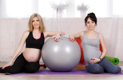 Pregnant women with large gymnastic balls. Two happy pregnant women,brunette and blonde,dressed in sportswear,execute a complex of exercises for pregnant women royalty free stock image