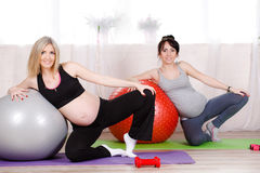 Pregnant women with large gymnastic balls. Two happy pregnant women,brunette and blonde,dressed in sportswear,execute a complex of exercises for pregnant women royalty free stock photography