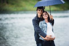 Pregnant woman and man holding an umbrella at the park in the drizzly day outdoors Stock Images