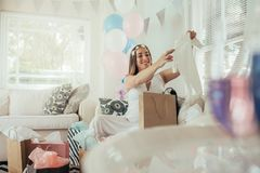 Pregnant woman opening a new gift after baby shower. Pregnant women opening a new gift after baby shower party at home. Expecting mother looking at baby clothes stock image