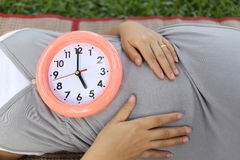 Pregnant women show clock on her belly to tell the time. Royalty Free Stock Images