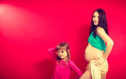 Pregnant woman showing belly and her daughter Royalty Free Stock Images