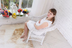 Pregnant women sit on a chair relaxing Stock Photography