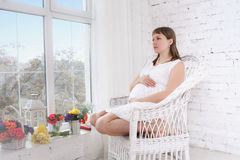Pregnant women sit on a chair relaxing. Pregnant woman sit on a chair relaxing near window Stock Images
