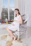 Pregnant women sit on a chair relaxing. Pregnant woman sit on a chair relaxing near window Royalty Free Stock Photography