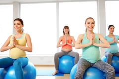 Pregnant women sitting on exercise balls in gym royalty free stock image