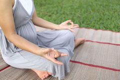 Pregnant women sitting meditation in the park. Royalty Free Stock Photos