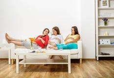 Pregnant women on sofa Stock Image
