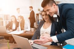 Pregnant woman works in office with colleagues. Young successful man helps pregnant girl at work. stock photography