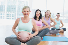 Pregnant women in yoga class sitting on mats touching their bumps Royalty Free Stock Photo