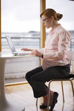 Pregnant and working variations. Young pregnant woman working at her laptop in an office royalty free stock image