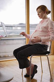 Pregnant and working variations. Young pregnant woman working at her laptop in an office feeling her bump stock photography