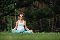 Pregnant yoga in the lotus position on the forest background. in the park  the grass  mat, outdoor, health woman. Stock Photography