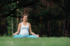 Pregnant yoga in the lotus position on the forest background. in the park  the grass  mat, outdoor, health woman. Stock Photos