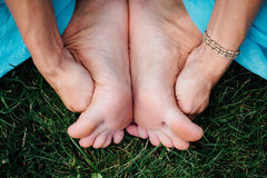 Pregnant yoga in the lotus position. in the park on the grass, doing exercises, stretching, outdoor, . feet close-up Stock Image