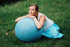Pregnant yoga prenatal doing different exercises with fitball. in park on the grass, breathing, stretching, Pilates. Pregnant yoga prenatal maternity doing Stock Image