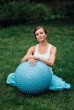 Pregnant yoga prenatal doing different exercises with fitball. in park on the grass, breathing, stretching, Pilates. Pregnant yoga prenatal maternity doing Stock Photo