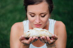 Pregnant yoga prenatal maternity with freshly baked homemade bread in hands in park on the grass. royalty free stock images