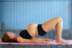 Pregnant Yoga. Strong and fit young pregnant woman doing bridge pose (setubandhasana) in prenatal yoga class royalty free stock images