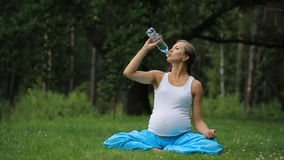 Pregnant yoga woman drinking water from a bottle, in the lotus position. park ,grass ,.outdoor, forest. stock footage