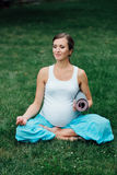 Pregnant yoga woman in the lotus position with mat portrait in park on the grass, breathing, stretching, statics. Royalty Free Stock Images