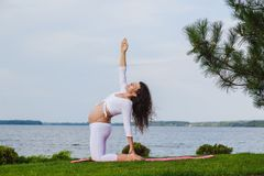 Pregnant woman is practicing yoga beside river Royalty Free Stock Photo