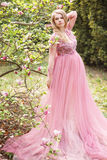 Pregnant young beautiful woman in pink lace long dress in a flowering garden Stock Photos
