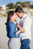 Pregnant young couple interacting facing each other, standing outdoors, beach scene. Embracing, with casual wear Royalty Free Stock Photography