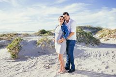 Pregnant young couple interacting, standing outdoors, beach scene. Embracing, with casual wear full length shot Royalty Free Stock Photo