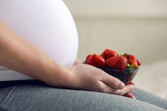 Pregnant young girl holding a plate of strawberries Stock Photos