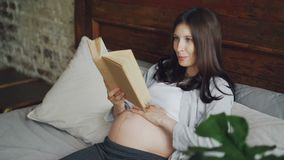 Pregnant young lady is reading book aloud and stroking her baby bump with love and tenderness, smiling girl is enjoying. Literature and resting. Pregnancy stock video footage