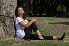Pregnant young mum dreaming, sitting near a tree Royalty Free Stock Photo