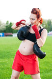 Pregnant young woman with boxing gloves. On stadium Royalty Free Stock Photos