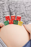 Pregnant young woman with cubes on her belly Royalty Free Stock Photos