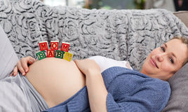 Pregnant young woman with cubes on her belly Stock Photos